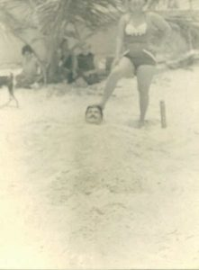 Fun at the Beach in Cuba. Carmen Permuy steps on the head of her husband, Benito Permuy, as he is buried in the sand.