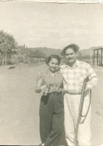 Carmen and Benito Permuy in Cuba before Castro. A relaxing day, Carmen with a drink in hand; Benito holding a rifle.