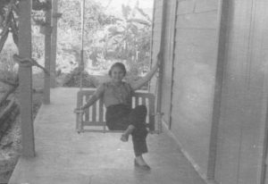 Carmen Canete Permuy sits on a porch swing in Cuba
